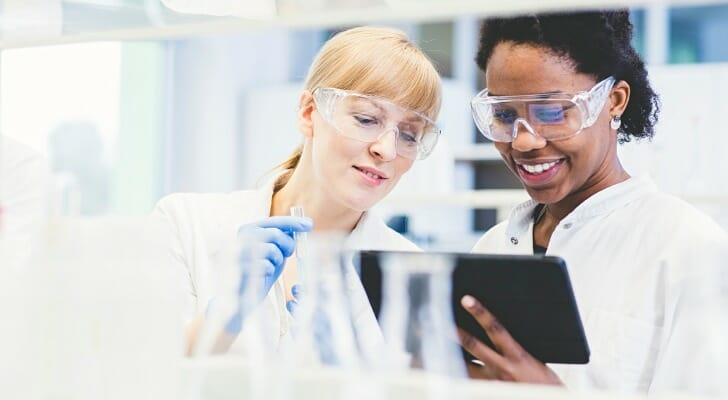 Image shows two scientists reviewing data in a lab. SmartAsset analyzed data across gender and race lines to find the best cities for diversity in STEM.