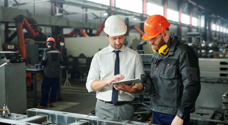 Image shows two workers wearing hard hats standing next to each other to consult a document in their workplace. SmartAsset analyzed data on income growth, job growth, manufacturing workforce and unemployment to find the best places to work in manufacturing.