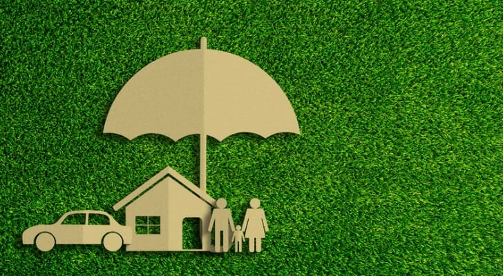 paper cutout of an umbrella over a house and car