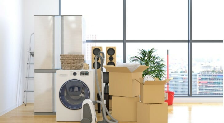Image shows boxes and appliances stacked in the middle of an otherwise empty apartment on moving day. SmartAsset analyzed IRS data to complete this year's study on where rich millennials are moving.