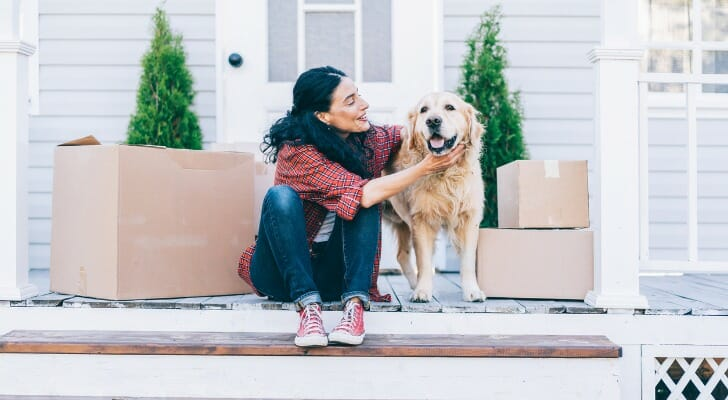 Images shows a young woman wearing a red plaid shirt, blue jeans and red sneakers sitting on white porch steps and petting an adult golden retriever. Moving boxes sit on either side of the woman and the dog. The dog is smiling. For this study, SmartAsset looked at data for 100 of the largest U.S. cities to find the most dog-friendly cities in the country.