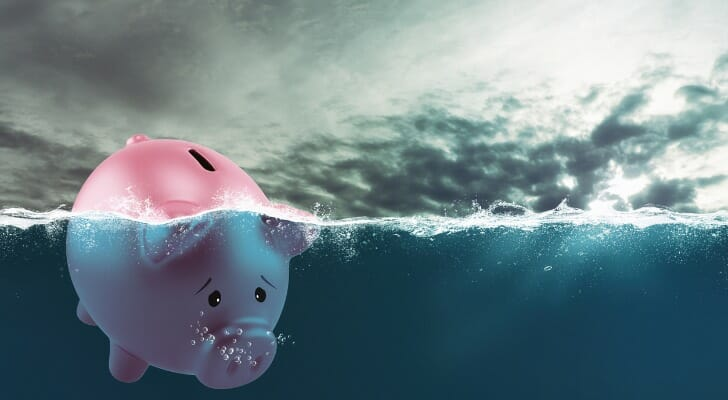 Picture of a piggy bank sinking beneath the surface of the sea.