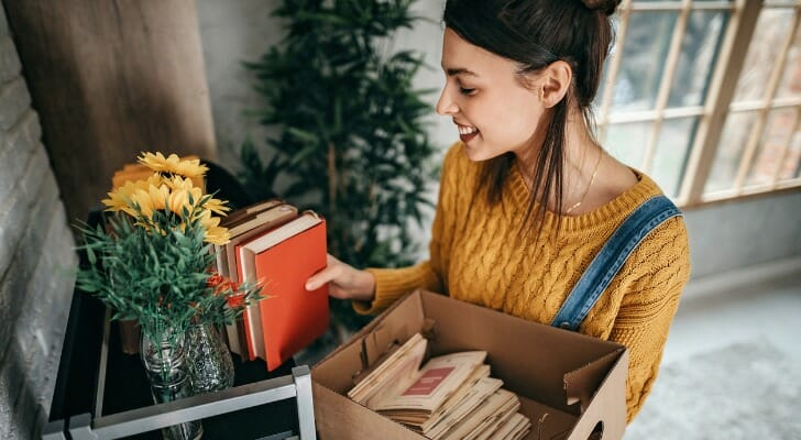 Image shows a young adult standing in their new apartment, arranging some books on a bookshelf in their apartment. SmartAsset analyzed data on rent, housing units and earnings to conduct this year's study on the cities where renters can afford to live alone.