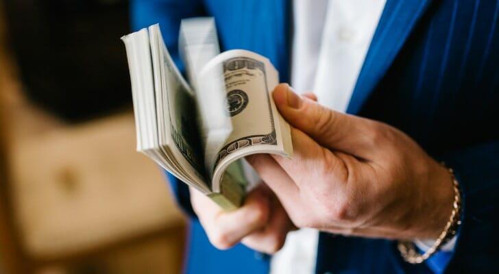 Man holding large wad of bills