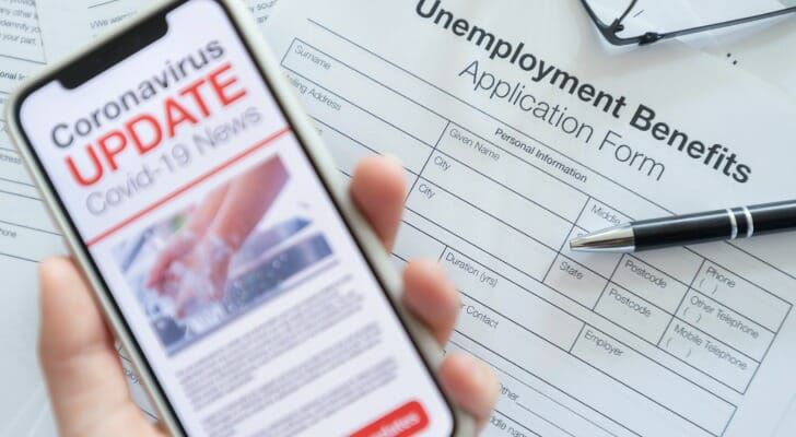 """Image shows a hand holding a mobile phone displaying text that reads """"Coronavirus Update"""" above a blank unemployment benefits application. SmartAsset analyzed BLS data to find where unemployment has increased the most and least from the start of COVID-19 to August 2020."""
