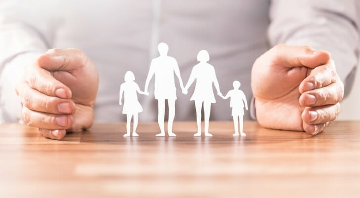 Pair of hands protecting cutout figures of family members