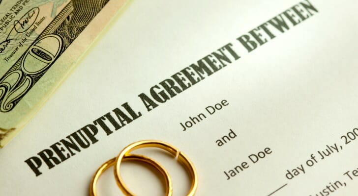 A prenuptial agreement with a set of wedding rings on top