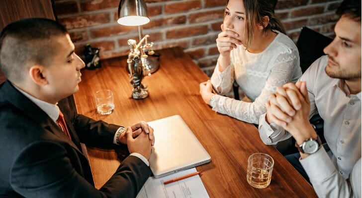 Engaged couple meets with lawyer about a prenuptial agreement