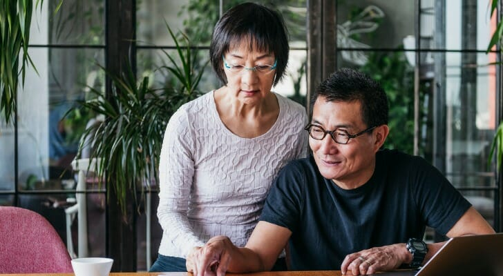 Image shows two retirees sitting in front of a laptop and reviewing paperwork. SmartAsset used Census Bureau data in order to conduct its latest study on the states and cities where retirees are moving.