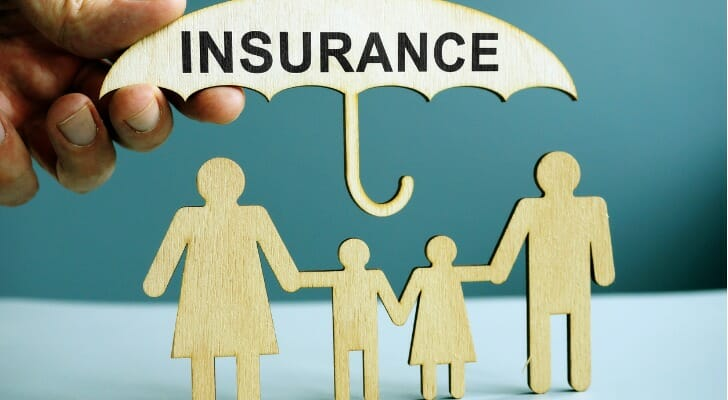 """""""INSURANCE"""" umbrella over figures of family members"""
