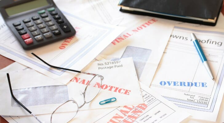 Image shows several unpaid bills on the table, next to a calculator and a closed checkbook. SmartAsset analyzed several data sources to conduct this study on the states where residents are financially hurting the most.