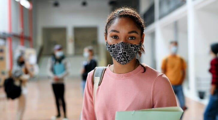 Image shows a student standing in a school hallway, holding notebooks and wearing a face mask to protect from COVID-19 and other viruses. SmartAsset analyzed various data sources to conduct its latest study on the top U.S. states for higher education.