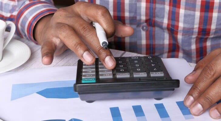 Man calculates benefits of a tax-deferred account