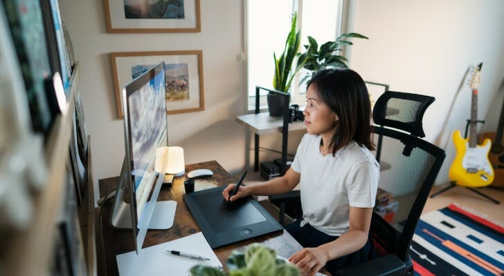Image shows an Asian American person working from home. SmartAsset analyzed various data in order to conduct its study on where Asian Americans fare best economically.