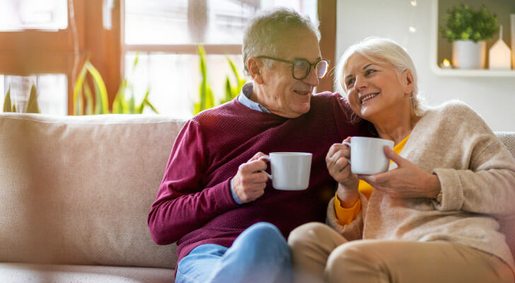 Image shows two adults who are senior citizens sitting on their couch and enjoying coffee. SmartAsset analyzed various data to conduct its latest study on where seniors are most and least financially secure.