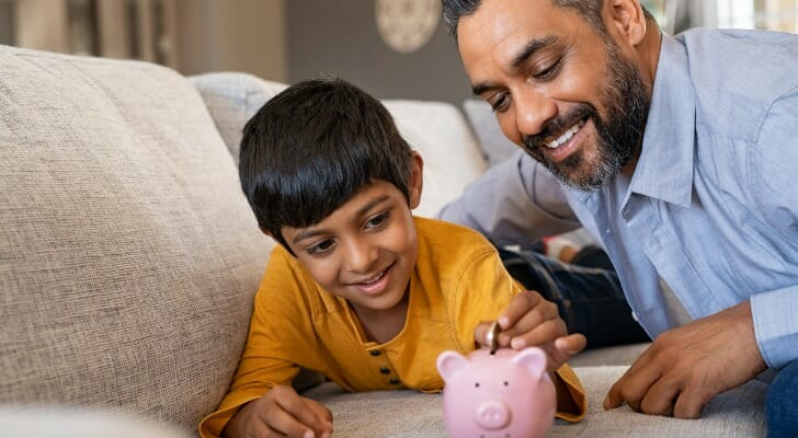 Father and son put money in a piggy bank