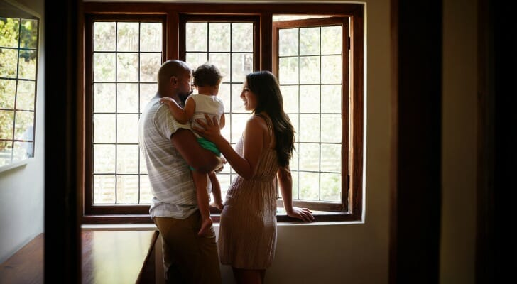 Image shows a small family - two parents and their child - standing in their home. SmartAsset analyzed data from various sources to conduct its latest study on the best cities for an affordable family home.