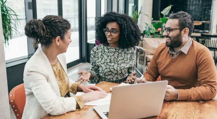 Image shows a financial advisor speaking with two potential clients. In this study, SmartAsset surveyed about 160 advisors who are part of our advisor matching platform to ask about what they see as their value proposition.