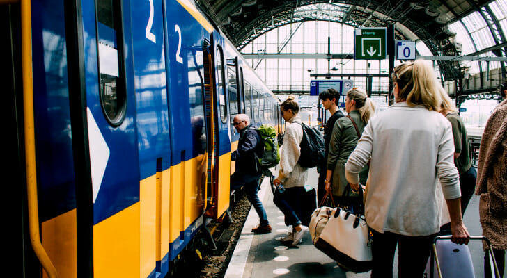 Image shows commuters boarding a public train. For the 2021 edition of this study, SmartAsset identified the places where people spend the most on transportation.