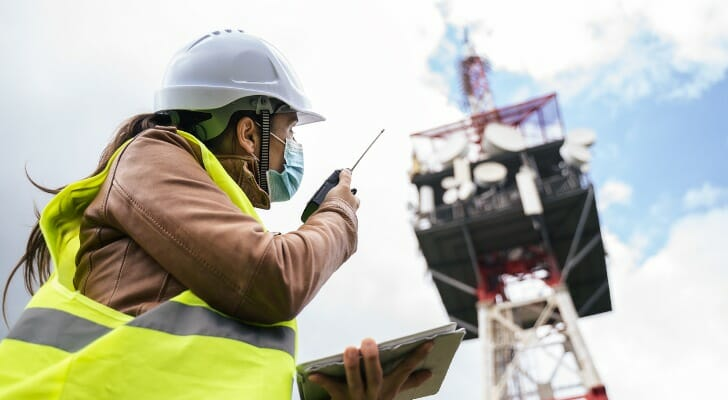 Image shows an engineering wearing a hard hat and a protective face mask working near a telecommunications tower. SmartAsset analyzed various data sources to identify the states with the best infrastructure.
