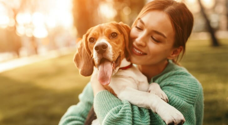 Image shows a pet parent playing with their dog. SmartAsset analyzed data from various sources to identify and rank the most dog-friendly cities in America.