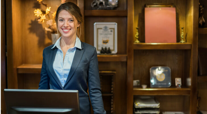 """Image shows a hospitality industry worker standing at a concierge desk. SmartAsset used various data sources to conduct its latest study, """"Where Leisure and Hospitality Jobs Are Recovering Fastest."""""""