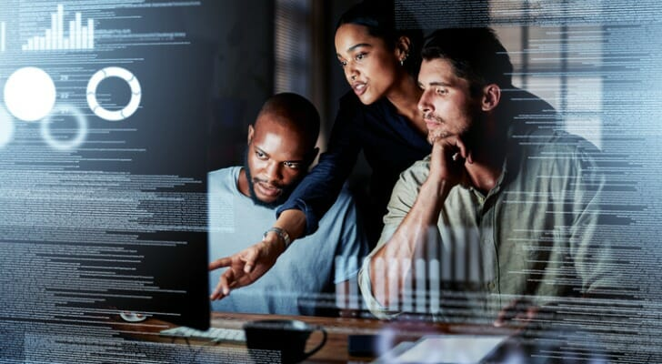 Image shows tech workers having a conversation while looking at a screen. SmartAsset analyzed data to identify the best places for tech workers in this study.