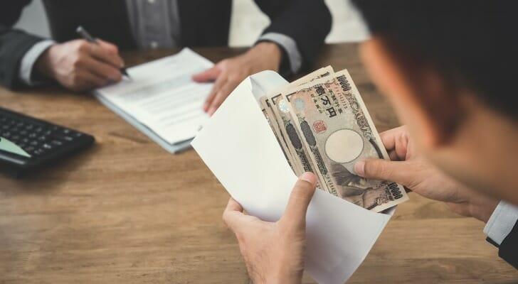 Man holding lots of Japanese yen bills