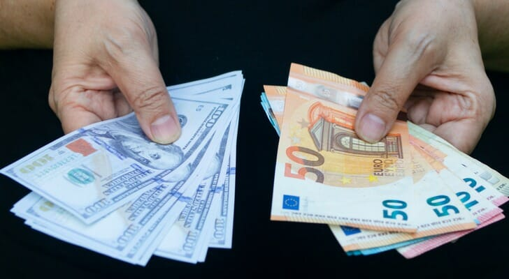 Man holding U.S. dollars and euro bills
