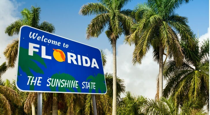 """Image shows a sign that reads """"Welcome to Florida: The Sunshine State"""" against a background of palm trees and a sunny blue sky. SmartAsset analyzed IRS data to determine where upper-middle-class people are moving."""