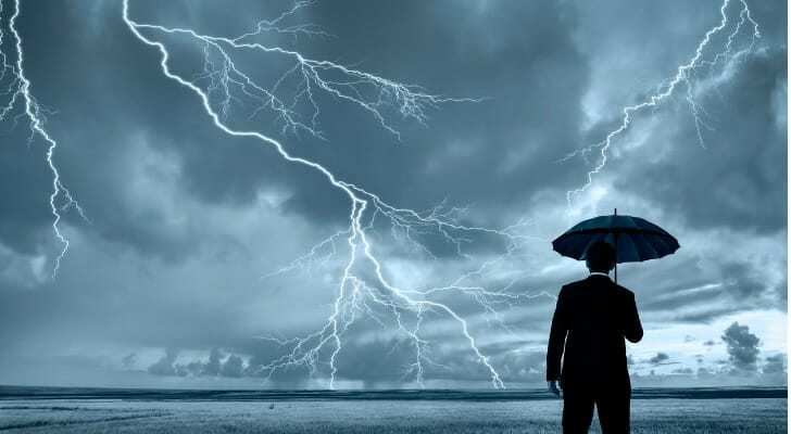 Man standing with an umbrella while lightning strikes in front of him.