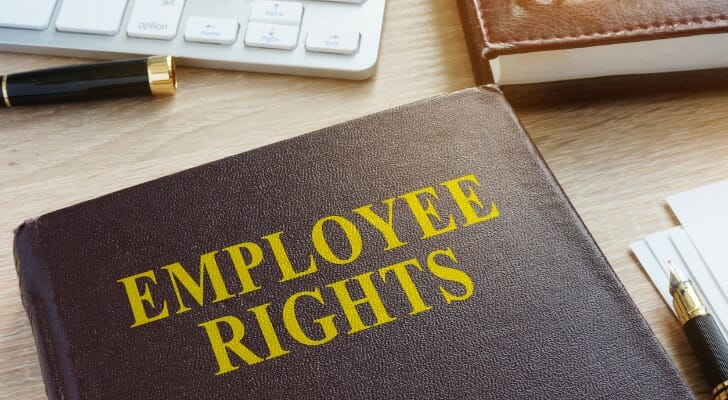 """Image shows a brown leather-bound book with """"EMPLOYEE RIGHTS"""" written on the cover in yellow lettering; the book sits on a desk with other office supplies such as a keyboard, notebook and pen. SmartAsset analyzed data on various metrics to conduct its 2020 study on the states with the strongest unions."""