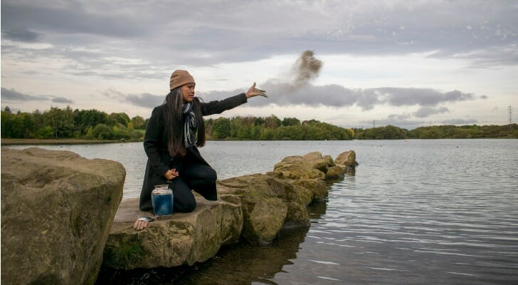 Woman scattering ashes from a cremated love one into the sea