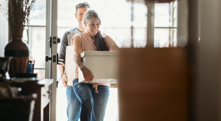 Image shows two adults carrying moving boxes into a new home. SmartAsset analyzed data on various factors to find the cities where the average household can afford the most and least home.