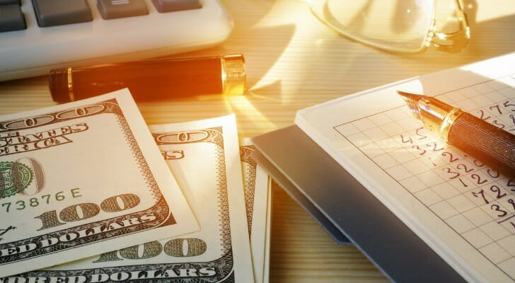 Cash and a calculator on a desk represent the need for more small business stimulus aid.