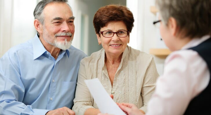 A couple speaks to a financial advisor for help planning their retirement in 10 years.