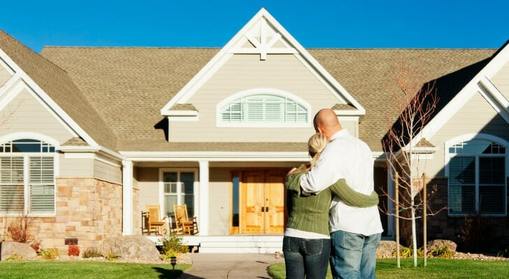 Image shows a couple standing arm in arm with their backs facing the camera as they admire their new home. SmartAsset analyzed IRS migration data to find the states to which rich Generation Xers are moving.