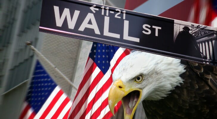 A photo of a bald eagle, two Amercan flags and a street sign that says Wall Street