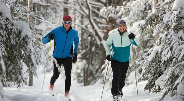 A couple cross-country skiing through a wooded snowscape in Michigan.