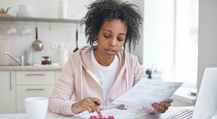 Image shows a woman sitting at a table with a calculator and bills in front of her; she is squaring away her latest financial statements. SmartAsset analyzed various data to identify where Americans are most and least financially literate.