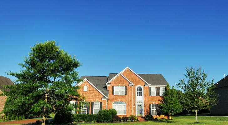 Image shows the facade of a brick home with a gray roof among some trees in its front lawn. SmartAsset analyzed various data from various sources to rank the best cities for first-time homebuyers.