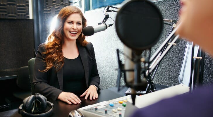 A woman speaks in a broadcast booth of a local television station.