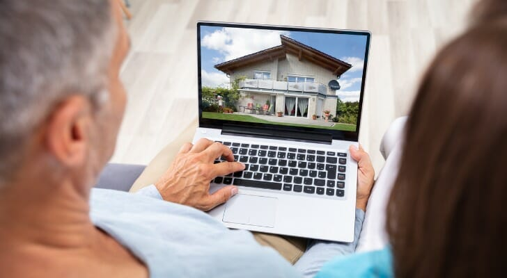 Couple looks online for a house for sale
