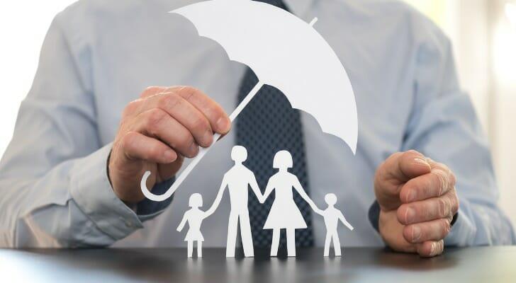 Man holding an umbrella over his family