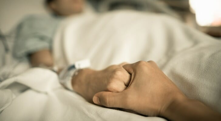 Man holds female hospital patient's hand