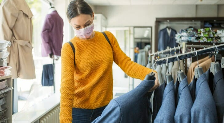 A customer in a clothing store wears a mask while shopping. In this study, SmartAsset takes a look at consumer spending in the U.S. during COVID-19.