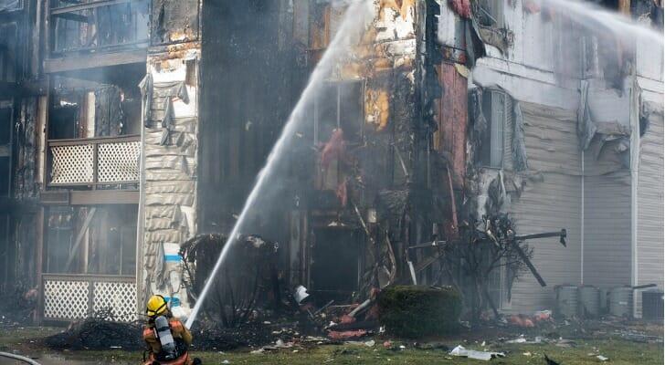 Fireman spraying water on a burning building