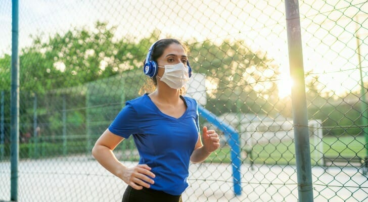 Image shows a young woman wearing a blue t-shirt, blue headphones, black leggings and a mask; she is jogging in a city park. SmartAsset analyzed data from various sources to find the best cities for runners.