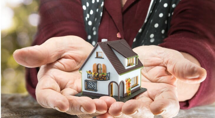 Small model of a house being held in the palms of someone's hands