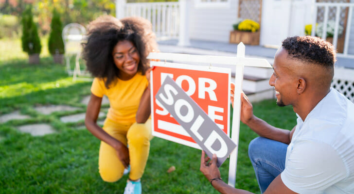 """Image shows two relatively young people changing the sign outside their home from """"For Sale"""" to """"Sold. SmartAsset found the places where more young residents are buying homes, based on 2009 and 2019 homeownership rates among residents younger than 35."""